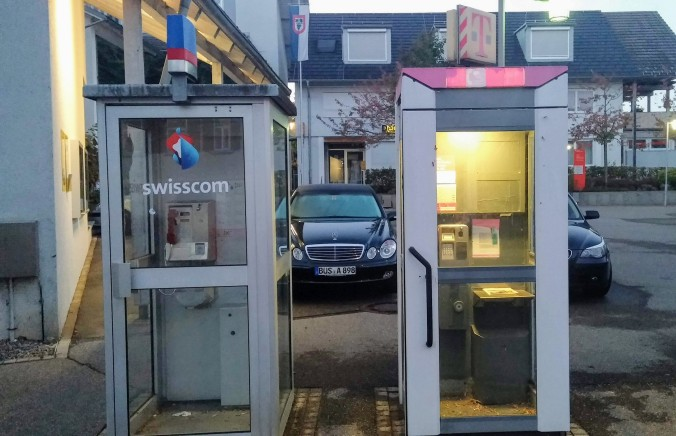 The side-by-side Swiss and German phone boxes in Buesingen